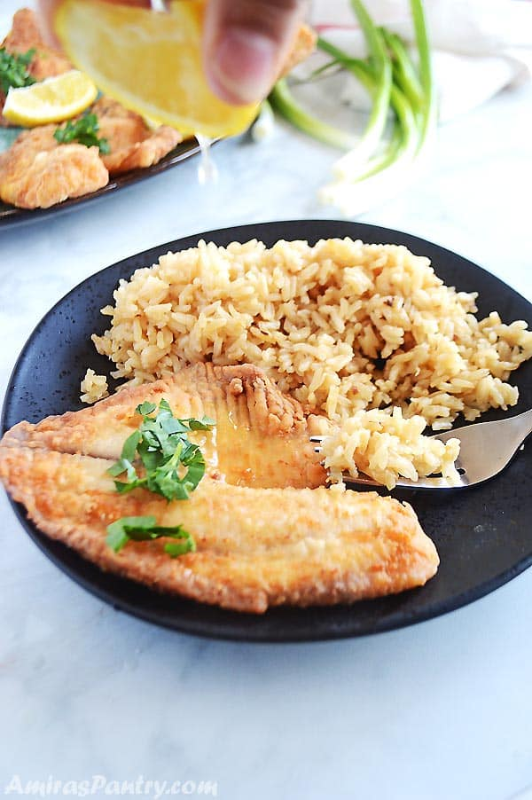 Hand squeezing lemon on piece of fried tilapia placed on a black plate with brown sugar and fork on the side.