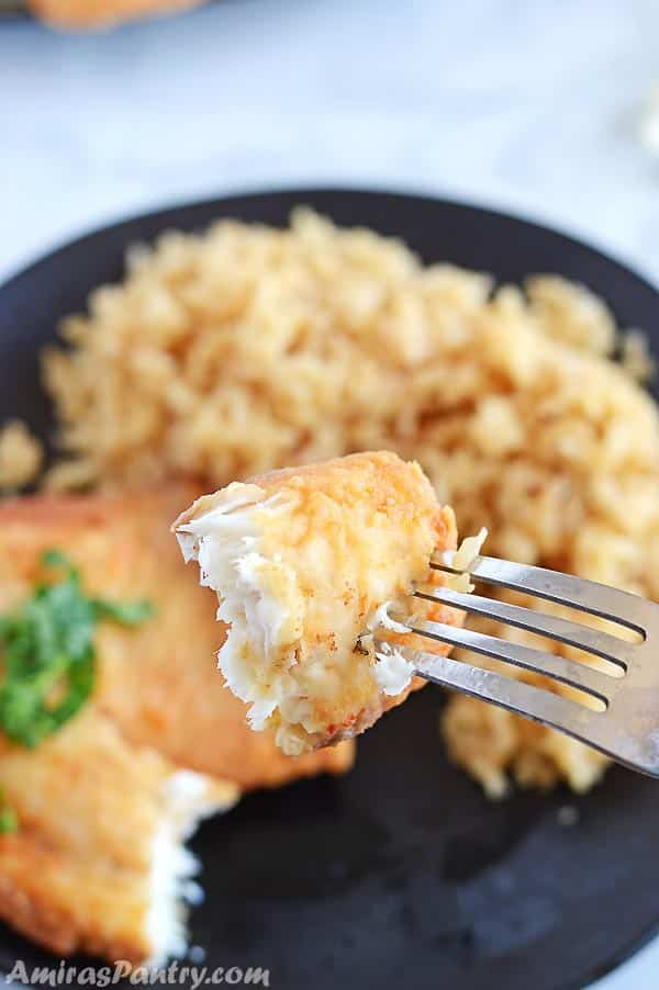 A fork holding a piece of fried tilapia with ablack plate with brown rice and the rest of the the tilapia piece in the background.