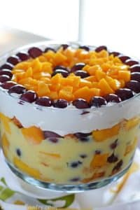 A big bowl of fruit trifle with mango pieces and grapes covering the top