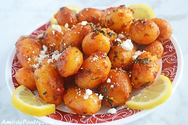 A white plate filled with spicy potato salad sprinkled with feta cheese and lemon rinds.