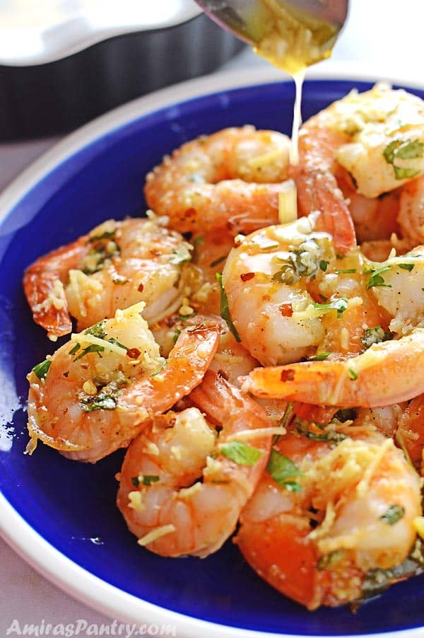 shrimp scampi on a blue plate with a spoon pouring some scampi sauce on top.
