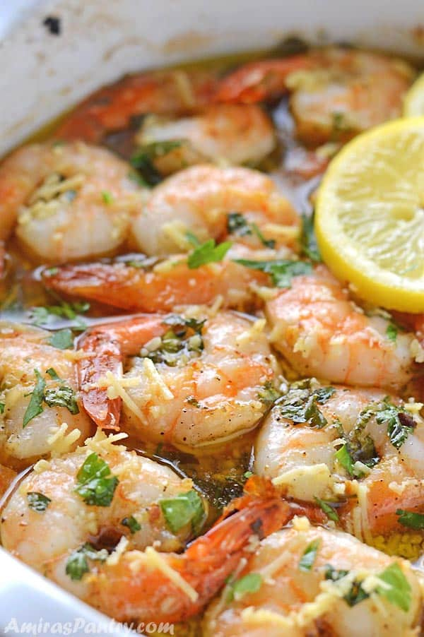 A white casserole of shrimp scampi garnished with pasrsley and lemon rinds.