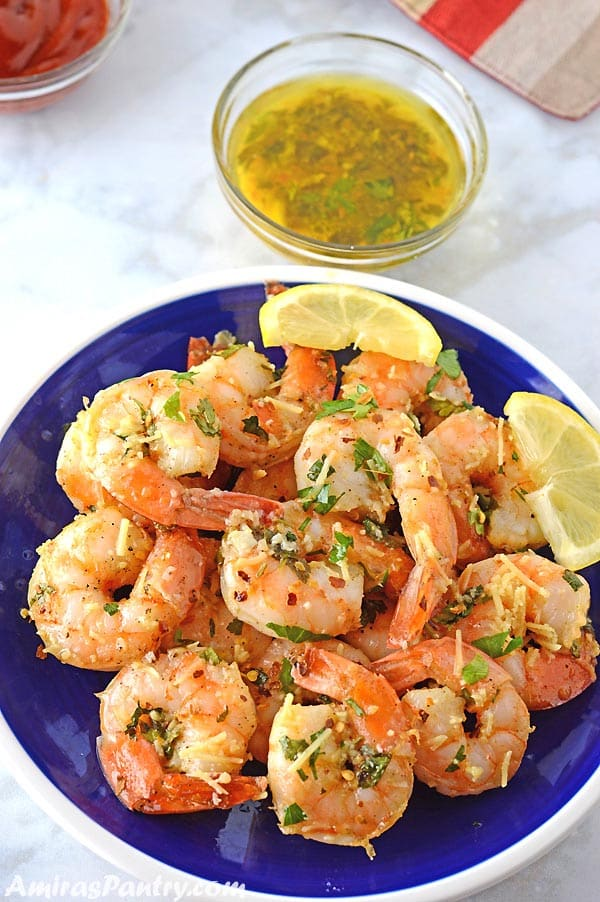 A blue plate with shrimp scampi garnished with parsley and lemon wedges with a small bowl of the sauce on the side.