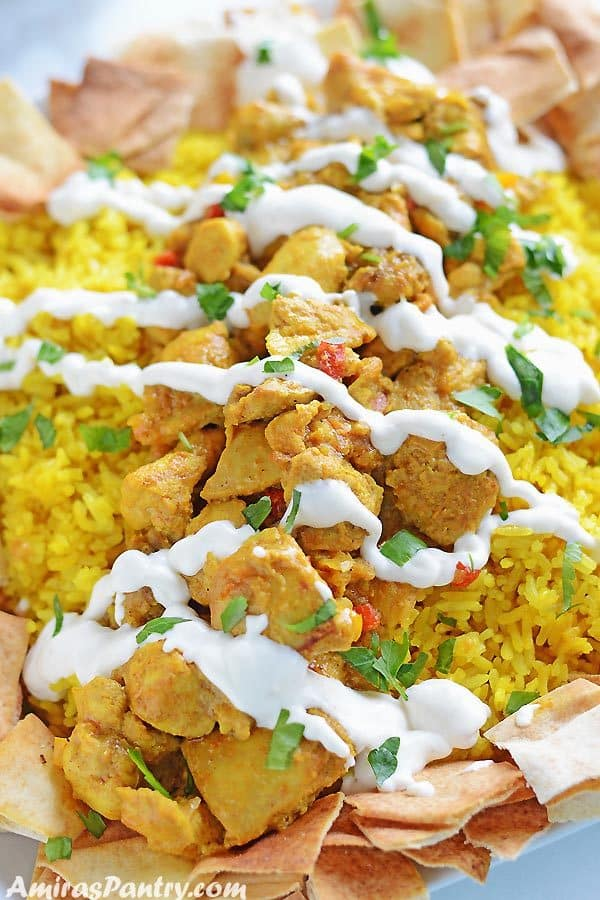 Yellow rice topped with chicken shawarma pieces and toasted bread in a platter and topped with shawarma white sauce.