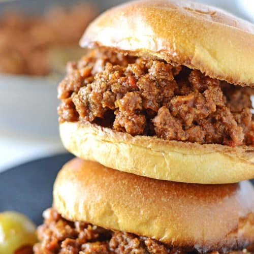 two sloppy joes sujuk sandwiches on top of eachother on a black plate
