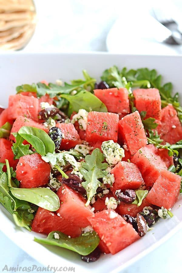 A white plate with watermelon and feta salas, some pita bread pieces are visible on the background