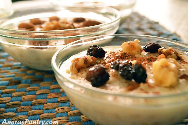 Two bowls of Ashure pudding garnished with nuts, cinnamon and raisins.