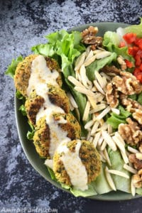 A green plate with baked flafel drizzled with some tahini sauce. Some lettuce and almonds on the plate as well.