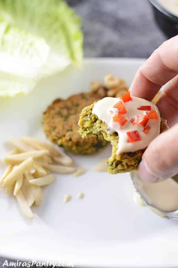 A hand holding one falafel patty covered with tahini sauce and some red bell pepper.