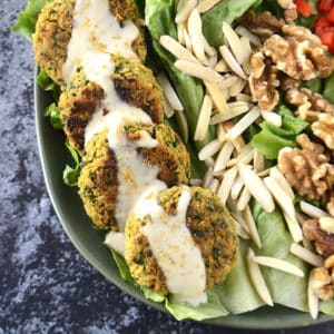 A green plate of baked falafel drizzled with tahini sauce with some lettuce and nuts on the plate.