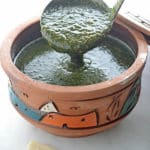 A ladle scooping molokhia from a clay pot on a white table with some pita bread on the side.