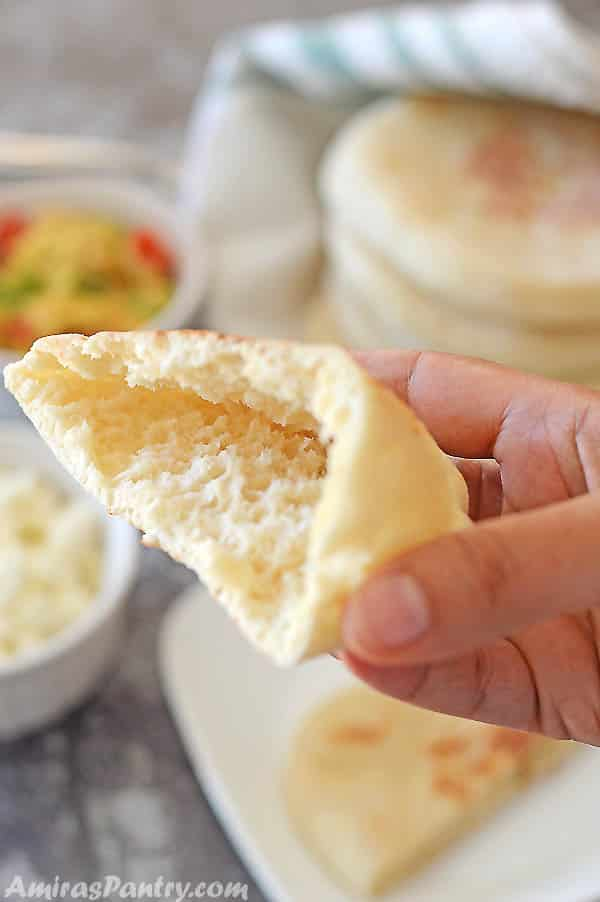 A hand holding half a pita opened and ready to be stuffed.