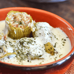A bowl of food on a plate, with zucchini and Yogurt