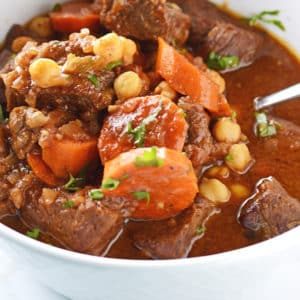 A bowl of food with Beef stew and carrots