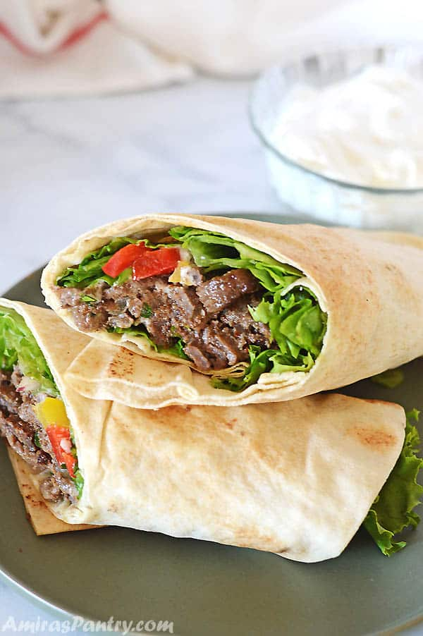 Beef Shawarma wrap on a dark green plate with a bowl of white shawarma sauce on the back.