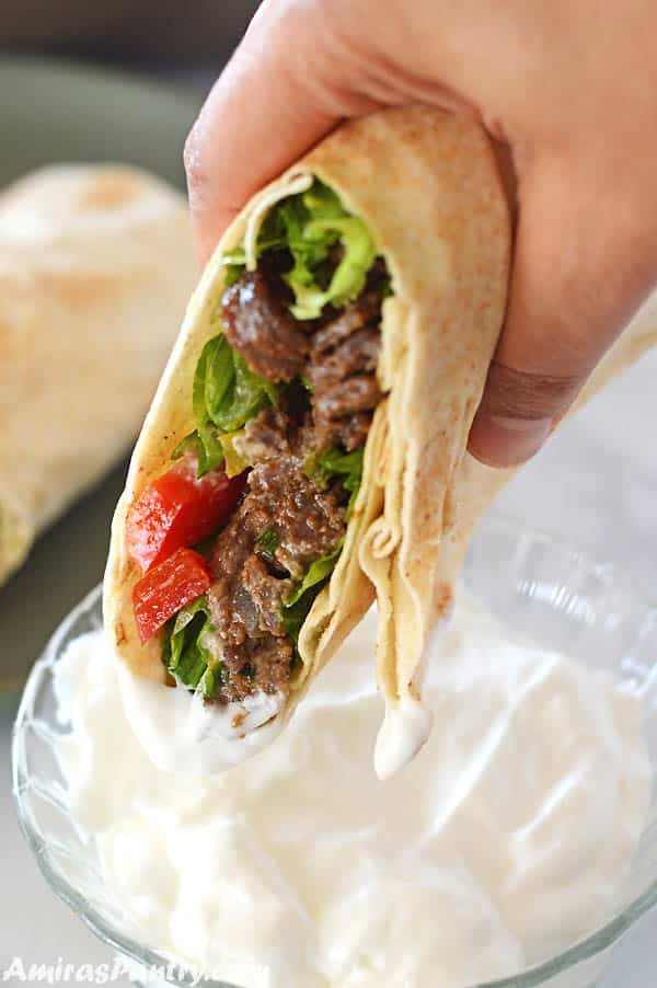 a hand holding beef shawarma wrap dipping it in garlic shawarma dip