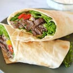 A wrapped sandwich on a plate, with Beef Shawarma