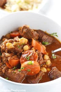 Beef stew in a white bowl with carrots and chickpeas and garnished with some chopped parsley
