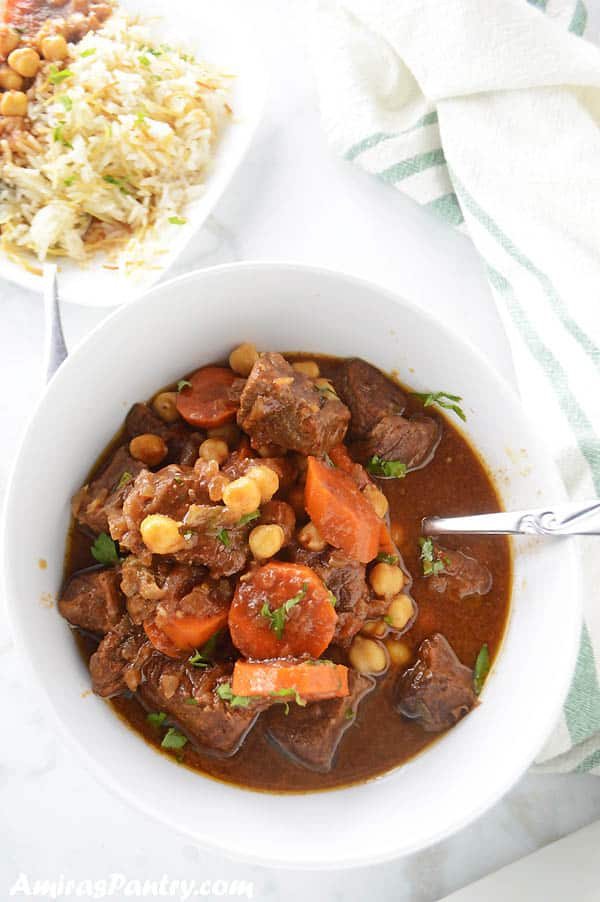 Beef stew in a white bowl on a marbled table with a plate of rice on the side.
