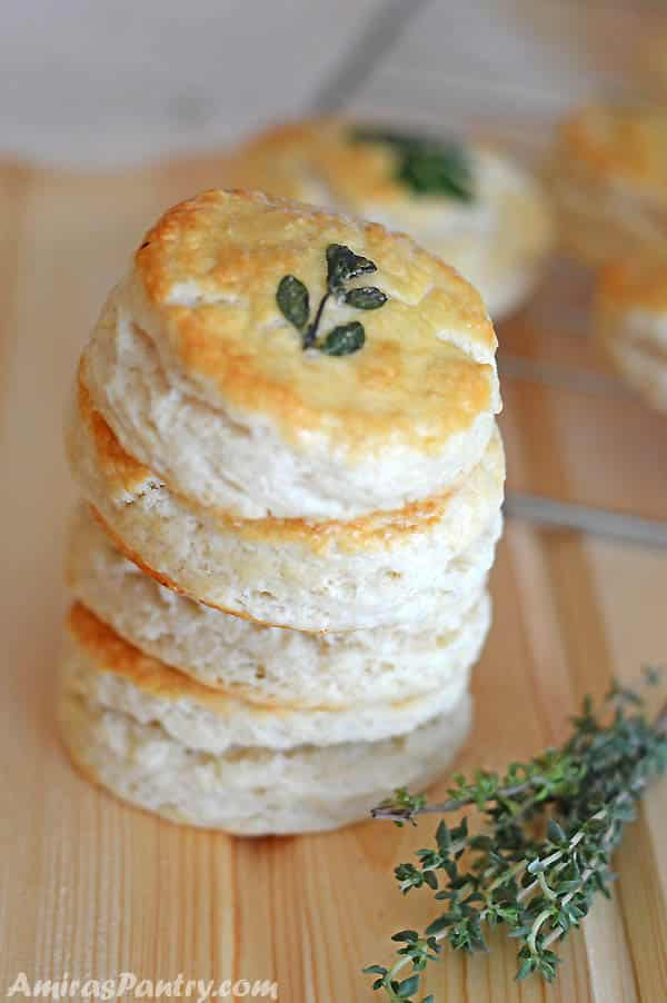 A stack of buttermilk cookies on a wooden table with green herbs on the side.