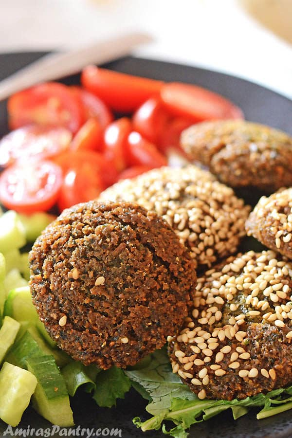 A black plate with falafel patties some of them are covered with sesame seeds with some greens and tomato on the side.