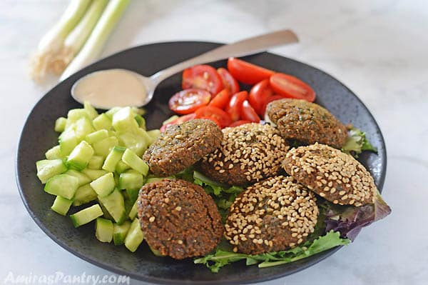 Falafel on a black plate with some diced cucmnber and tomato and a spoon with tahini on the side.