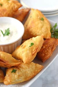 Samosas placed on a white table, farnished with parsely with a plate of yogurt dip in the middle.