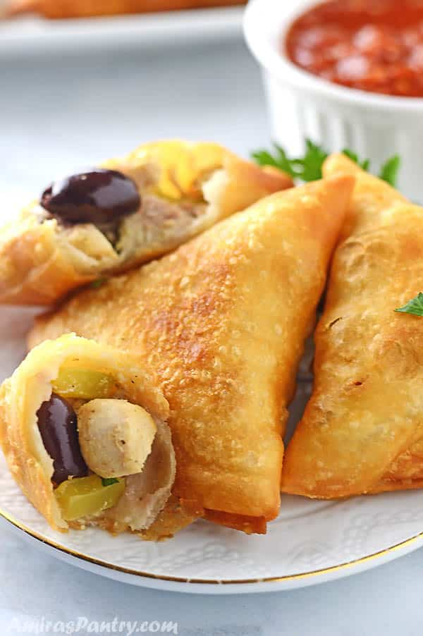 Chicken samosas cut in half to show filling place on a white table.