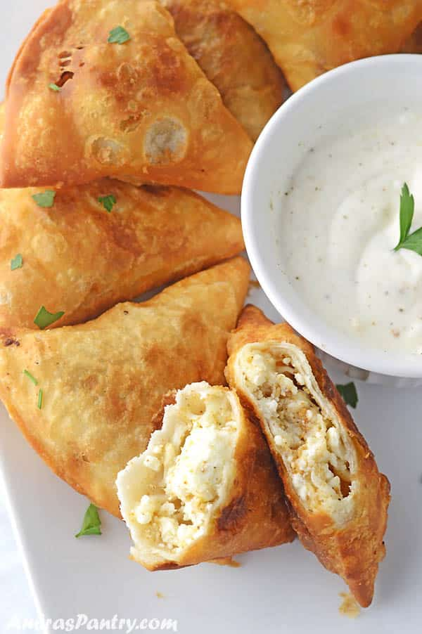 A white plate with friend samosas with a bowl of white sauce in the middle