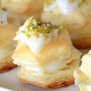 Shaabiyat stuffed and topped with cream and garnished with pistachios on a white plate.