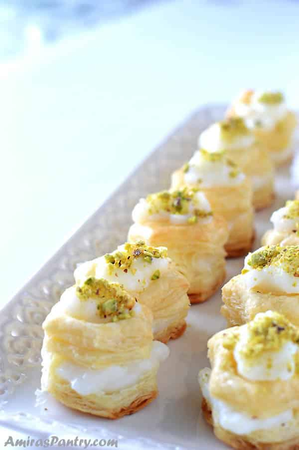 two rows of puff pastry squares filled with cream, garnished with pistachios and placed on a white serving platter.