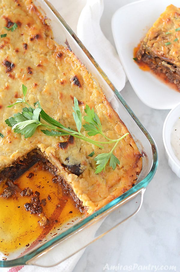 A whole pyrex pan of moussaka with one piece cut out and placed on a white plate on the side.