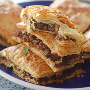A close up of a phyllo pie on a plate, stuffed with ground beef