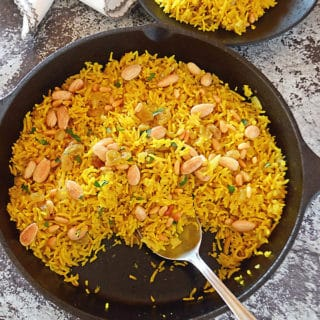 Yellow rice in a cast iron pan on a concret table with a black plate of yellow rice on the side