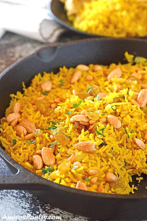 Yellow rice in a cast iron pan garnished with nuts and parsley.