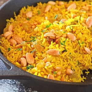 A pan of yellow rice with nuts