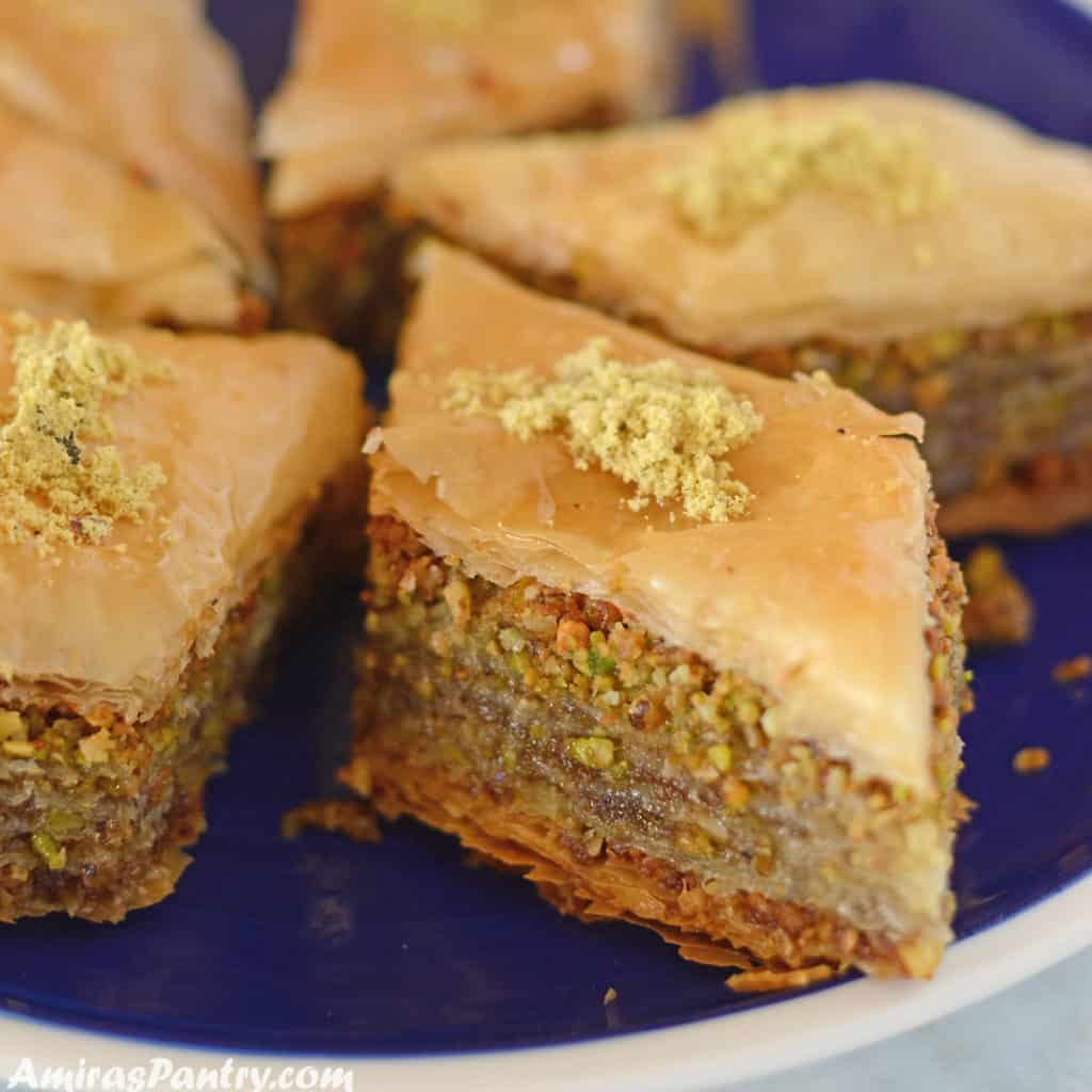 Baklava pieces placed on a blue plate and garnished with crushed pistachios.