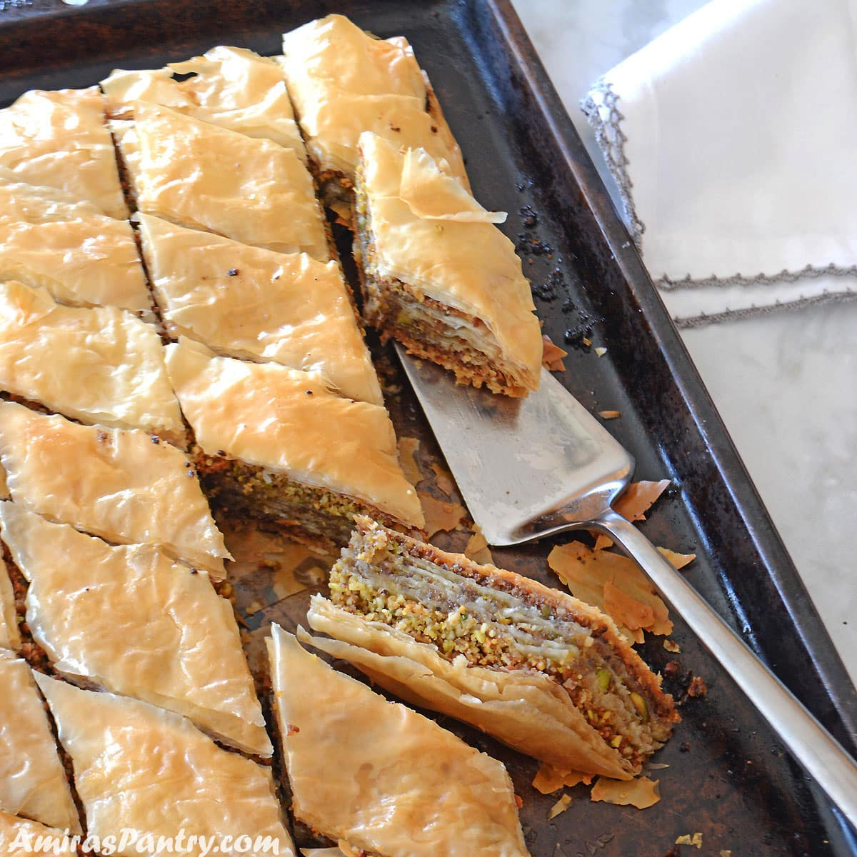 A dark baking sheet with baklava squares and one turned on its side to show the layers.