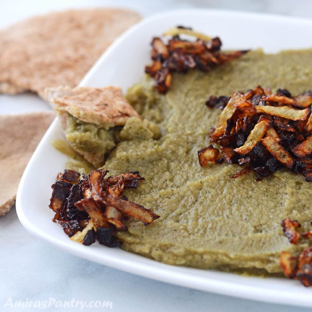 Green bissara dip on a white plate and garnished with fried onions.
