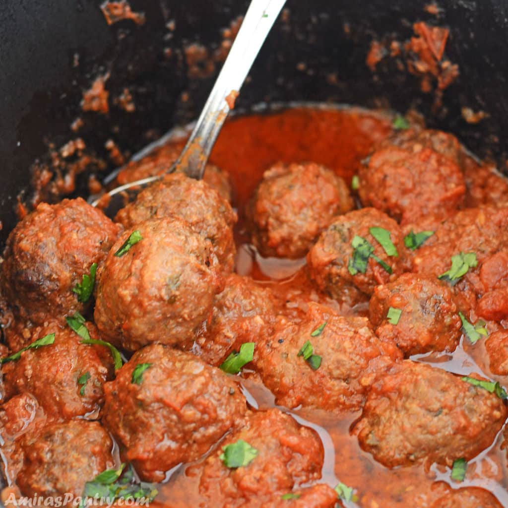 Crockpot meatballs in the deep black slow cooker ceramic pot with a spoon in it and a sprinkle of chopped parsley.
