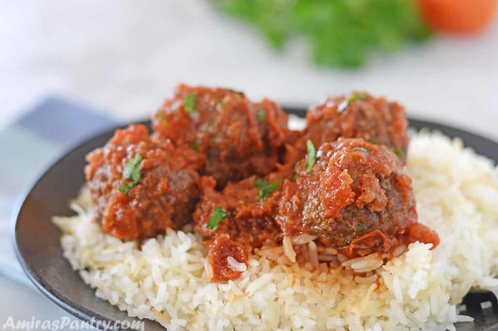meatballs with tomato sauce over a bed of rice on a black plate.