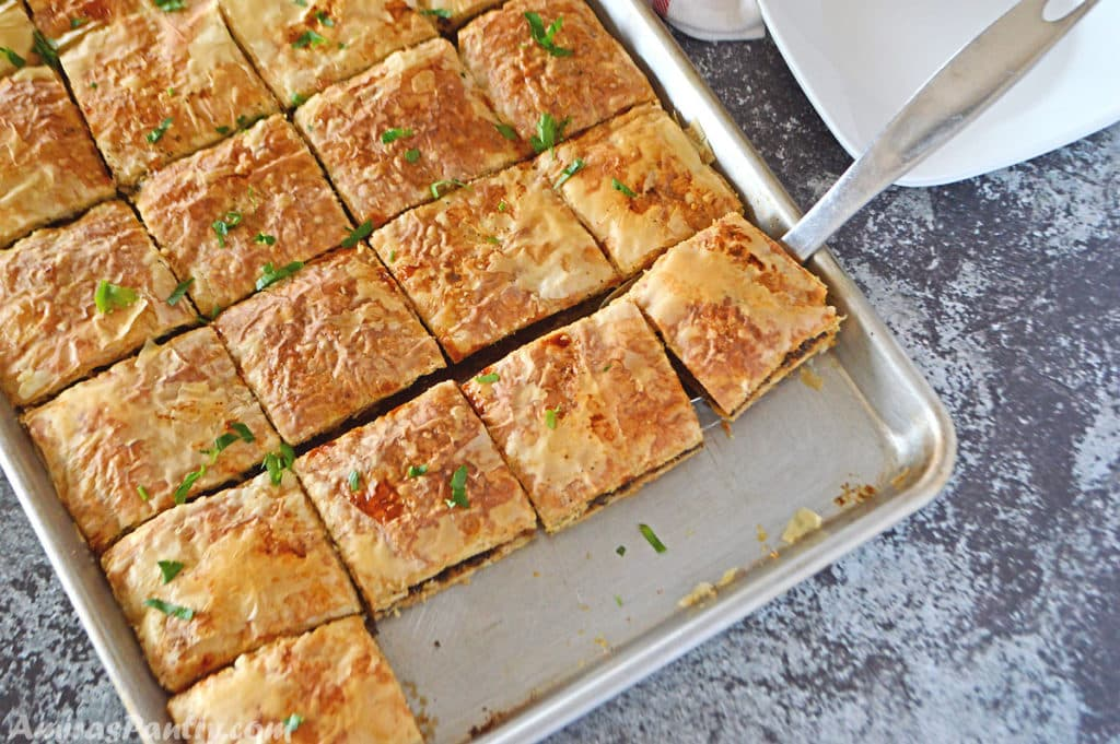 A baking sheet with phyllo squares cut side by side and placed on a dark grey table.