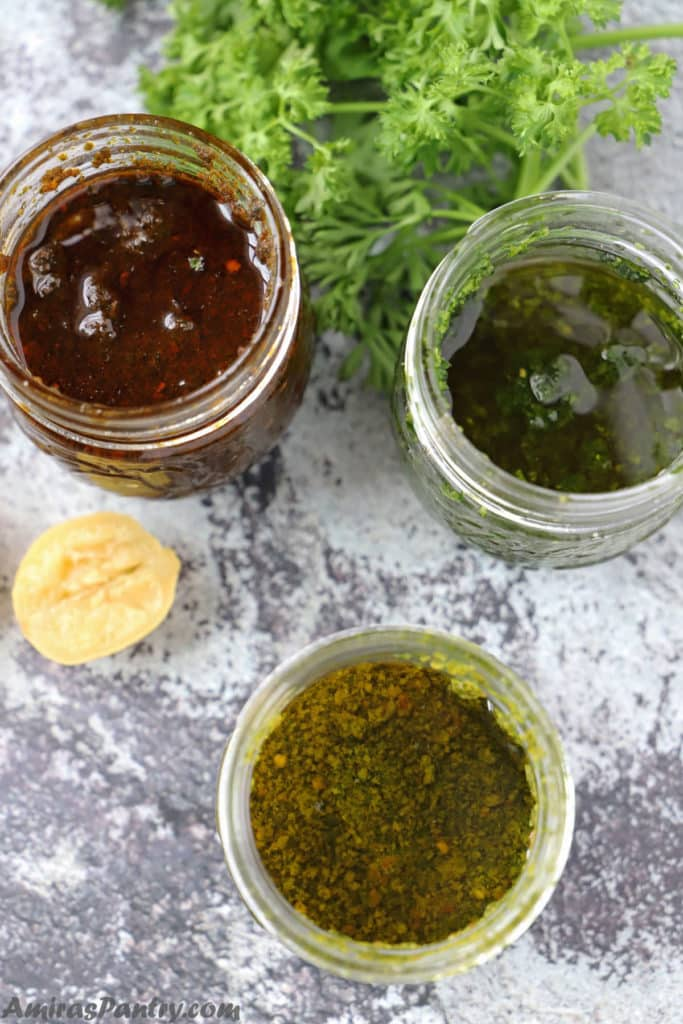 three jars of chermoula sauce, green chermoula and red chermoula placed on a concrete table with some parsley and half a lemon