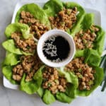 A bowl of salad, with Chicken and Lettuce
