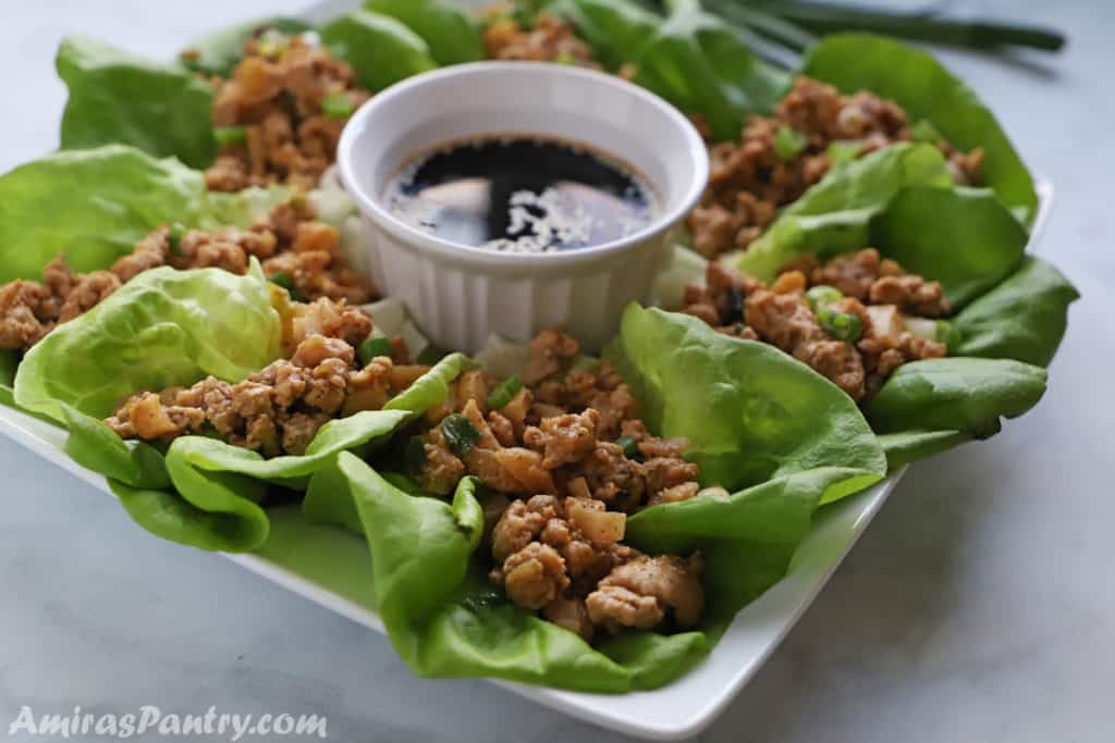 chicken lettuce wraps in a white platter with a bowl of sauce.