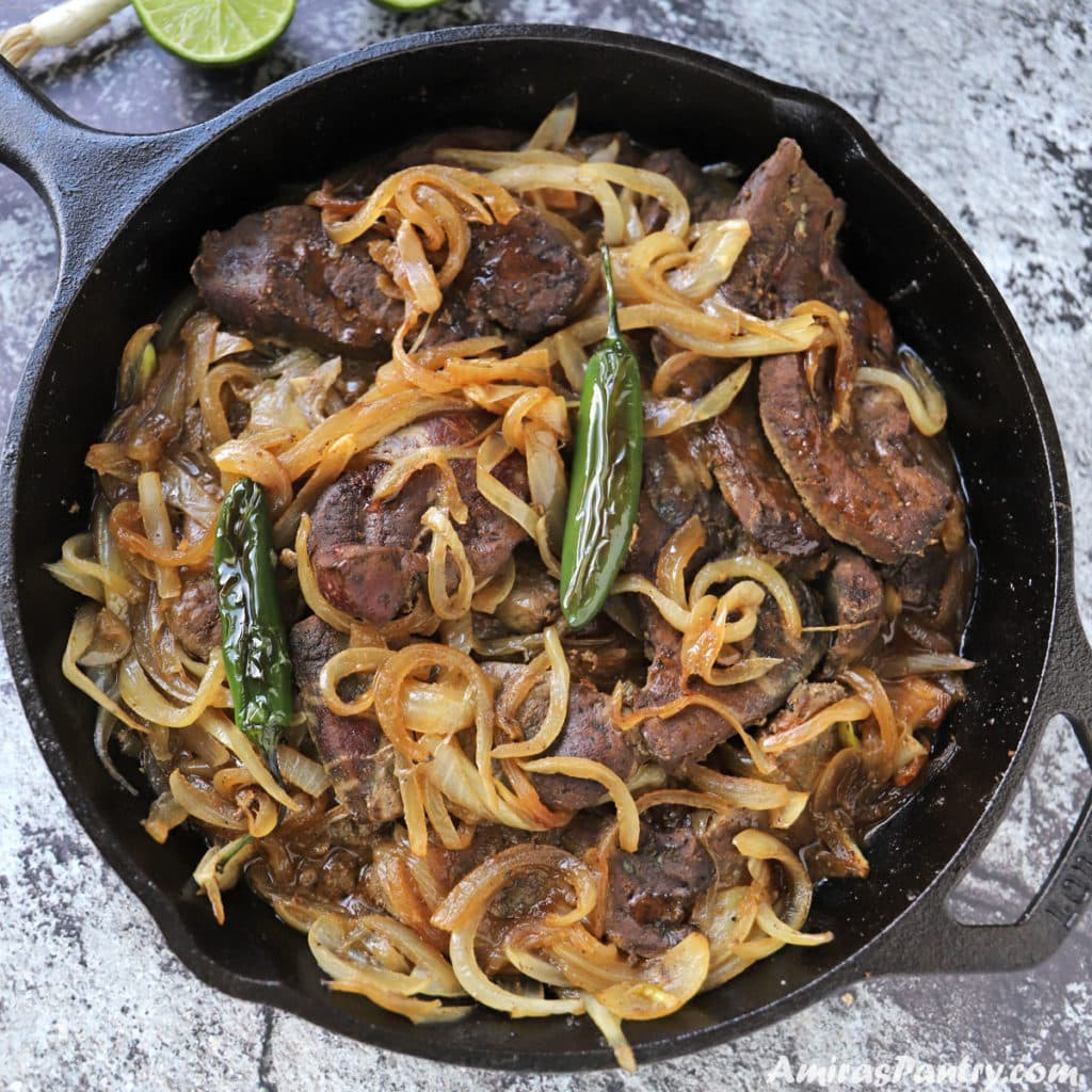 A cast iron skillet with beef liver and onions garnished with chili peppers on top.