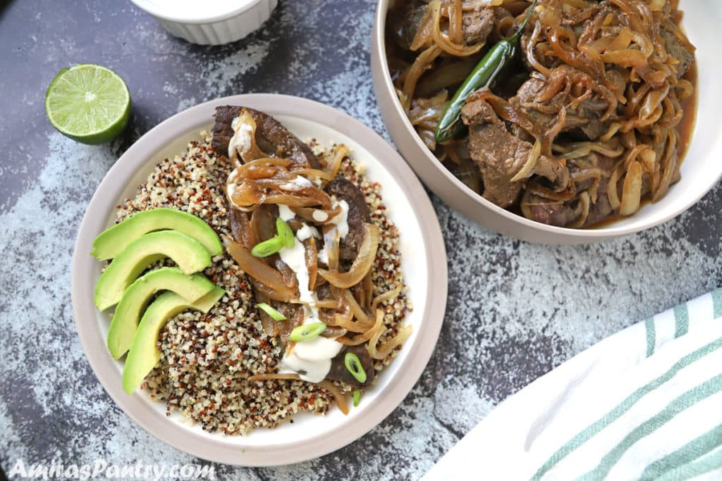 A plate with a serving of beef liver with some quinoa and sliced avocado on a concret table with half a lemon