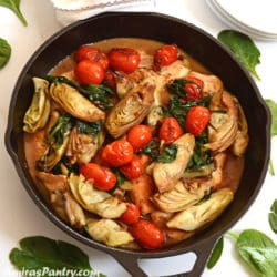 A cast iron skillet with lemon artichoke chicken and grape tomato on top placed on a white surgace.