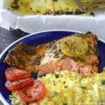 a piece of baked salmon with yellow rice on a blue plate