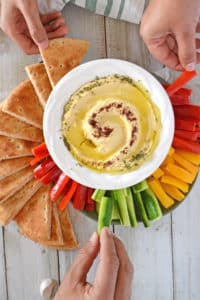 hands reaching out for veggie strips and pita wedges with a big bowl of hummus on the center.